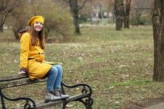 Den lyckliga tonårs- flickan sitter på bänken arkivfoto