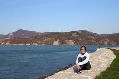 Den lyckliga tonårs- flickan sitter vid floden royaltyfri foto