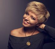 Den lyckliga toothy le kvinnan med kort blont guppar frisyren i gre fotografering för bildbyråer