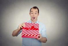 Den lyckliga toppna upphetsade förvånade unga mannen omkring som ska öppnas, packar upp den röda gåvaasken fotografering för bildbyråer