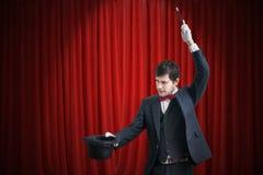 Den lyckliga trollkarlen eller illusionisten visar magiskt trick med hans trollstav Röda gardiner i bakgrund arkivbild