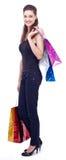 Den lyckliga ung flicka med shopping hänger lös royaltyfri fotografi