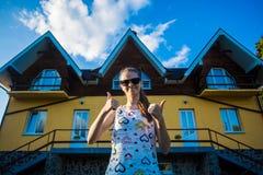 Den lyckliga unga affärskvinnan i solglasögon köpte ett stort hem för hennes familj Royaltyfri Fotografi