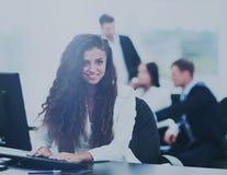 Den lyckliga unga affärskvinnan som ser behind, och hennes kollegor arbetar Arkivfoton