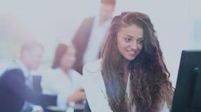 Den lyckliga unga affärskvinnan som ser behind, och hennes kollegor arbetar Fotografering för Bildbyråer