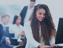 Den lyckliga unga affärskvinnan som ser behind, och hennes kollegor arbetar Royaltyfri Fotografi