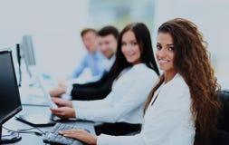 Den lyckliga unga affärskvinnan som ser behind, och hennes kollegor arbetar Royaltyfria Bilder
