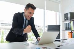 Den lyckliga unga affärsmannen är stå och se bärbara datorn royaltyfri foto