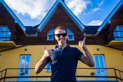 Den lyckliga unga affärsmannen i solglasögon köpte ett stort hem för hans familj Royaltyfri Fotografi