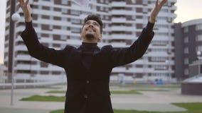 Den lyckliga unga affärsmannen i svart dräkt kastar dokumenterar ut utomhus- mot kontorsbyggnad lager videofilmer
