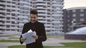 Den lyckliga unga affärsmannen kastar dokumenterar ut utomhus- arkivfilmer