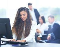 Den lyckliga unga affärskvinnan som ser behind, och hennes kollegor arbetar Arkivbild