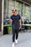 Den lyckliga unga arabiska mannen går på vägen, ler, och bruk ringer, manaen Arkivbilder