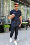 Den lyckliga unga arabiska mannen går på vägen, ler, och bruk ringer, manaen Royaltyfria Bilder
