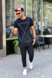 Den lyckliga unga arabiska mannen går på vägen, ler, och bruk ringer, manaen Royaltyfria Foton