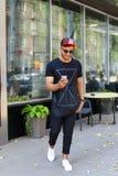 Den lyckliga unga arabiska mannen går på vägen, ler, och bruk ringer, manaen Arkivfoto