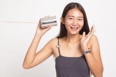 Den lyckliga unga asiatiska kvinnan att lyssna med tenn kan ringa arkivbilder