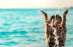 Den lyckliga unga asiatiska kvinnan i svart baddräkt kopplar av och tycker om ferie på den tropiska paradisstranden Flicka i vatt royaltyfri bild