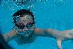 Den lyckliga unga asiatiska ungen med bad rullar med ögonen undervattens- Fotografering för Bildbyråer