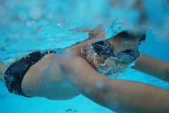 Den lyckliga unga asiatiska ungen med bad rullar med ögonen undervattens- Arkivfoto