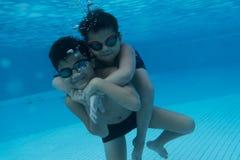 Den lyckliga unga asiatiska ungen med bad rullar med ögonen undervattens- Royaltyfria Bilder