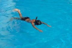 Den lyckliga unga asiatiska ungen med bad rullar med ögonen undervattens- Arkivfoton