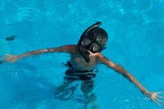 Den lyckliga unga asiatiska ungen med bad rullar med ögonen undervattens- Royaltyfri Fotografi