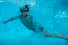 Den lyckliga unga asiatiska ungen med bad rullar med ögonen undervattens- Royaltyfri Foto