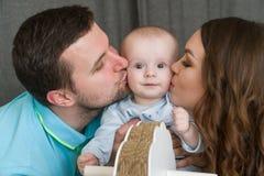 Den lyckliga unga attraktiva familjen med behandla som ett barn Arkivbilder