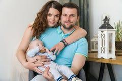 Den lyckliga unga attraktiva familjen med behandla som ett barn Arkivfoto