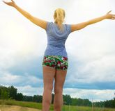 Den lyckliga unga blondinen som bär kortslutningar och enskjorta, står på vägen mot himlen med hennes utsträckta armar, exponerat royaltyfria foton