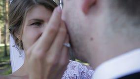 Den lyckliga unga bruden ser hennes brudgum lager videofilmer