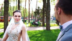 Den lyckliga unga bruden som g?r runt om den stilfulla brudgummen som fortfarande st?r i soligt, parkerar arkivfilmer