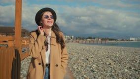 Den lyckliga unga brunetten går bara Pebble Beach i soligt väder lager videofilmer