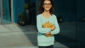 Den lyckliga unga brunetten i exponeringsglas ler och går i gatan stock video