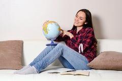 Den lyckliga unga brunettkvinnan drömmer om resande på semester med ett jordklot i händer på en vit soffa i rummet Arkivfoton