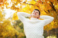 Den lyckliga unga Caucasian stiliga mannen som blir i höst, parkerar, sträckning och det rörande huvudet Lata höstdagar Arkivbild