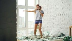 Den lyckliga unga damen har roligt sjunga i hårborste och att dansa banhoppning på säng som lyssnar till musik till och med hörlu arkivfilmer