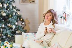 Den lyckliga unga damen med lockigt hår sitter nära julgranen royaltyfri bild