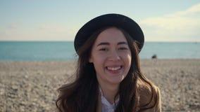 Den lyckliga unga damen tycker om varmt väder i solig strand, närbild av framsidan arkivfilmer