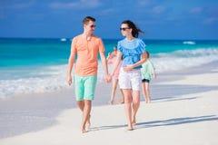 Den lyckliga unga familjen av fyra på en tropisk strand tycker om sommarsemester Royaltyfri Foto