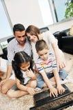 Den lyckliga unga familjen har ett gyckel med den hemmastadda bärbar dator arkivfoto