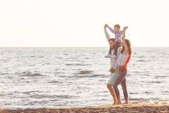 Den lyckliga unga familjen har gyckel på den körda stranden och hoppar på solnedgången Fotografering för Bildbyråer