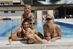 Den lyckliga unga familjen har gyckel på simbassäng Fotografering för Bildbyråer