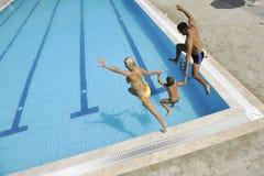 Den lyckliga unga familjen har gyckel på simbassäng Arkivbilder
