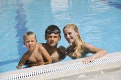 Den lyckliga unga familjen har gyckel på simbassäng Arkivfoton