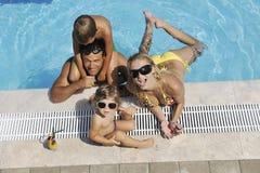 Den lyckliga unga familjen har gyckel på simbassäng Arkivbild
