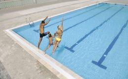 Den lyckliga unga familjen har gyckel på simbassäng Royaltyfri Bild