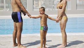 Den lyckliga unga familjen har gyckel på simbassäng Royaltyfria Foton