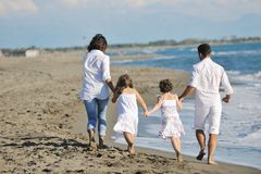 Den lyckliga unga familjen har gyckel på strand Royaltyfri Bild